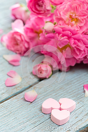 Gentle pink rose and heart on wooden table