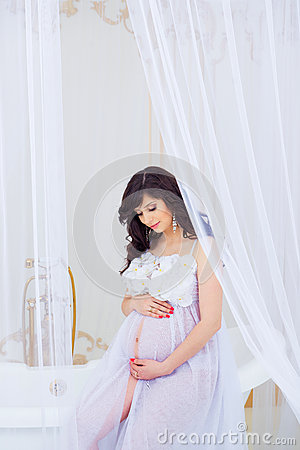 Free Gentle Pregnancy. Beautiful Pregnant In Light White Dress With Orchids Stock Images - 93394954