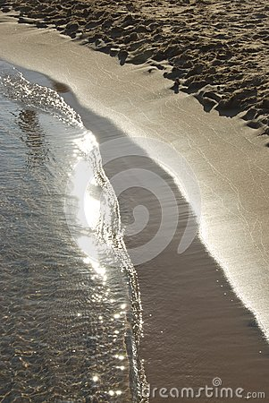 Gentle surf coming onto a sandy beach.