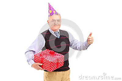 A gentleman with party hat holding a gift and giving a thumb up