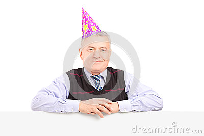 Gentleman wearing party hat and posing behind a panel