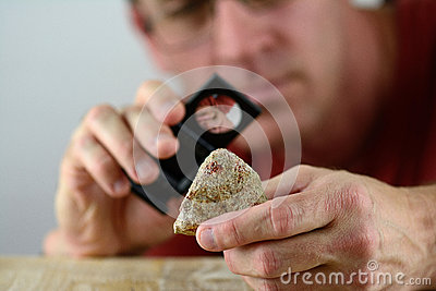 A geologist inspecting a piece of rock