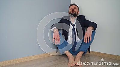 Geopende bebaarde man in untiele formele kleren zit in een leeg appartement De effecten van het Covid-19-virus op het stock video