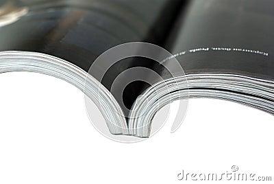 Geopende tijdschriftclose-up op witte achtergrond.