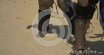 Gepanzerte Füße der Krieger, das auf dem Sand an der Arena kämpft stock video