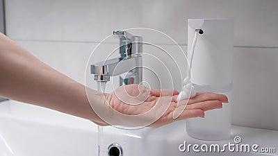 Gerador automático de espuma coloca em mãos a dose desejada de sabão Tecnologia moderna no banheiro Mãos femininas filme