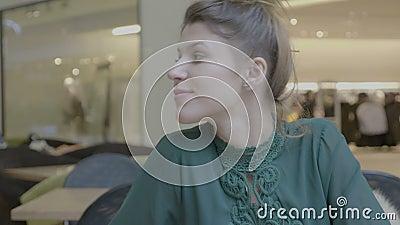 Gerente de vendas fêmea que descansa após o cappuccino bebendo do trabalho em um shopping que sorri e que olha a câmera - vídeos de arquivo