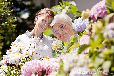 Geriatric nurse with elderly woman in the garden