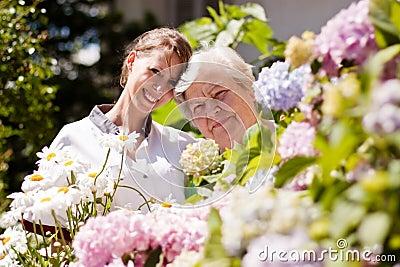 Geriatric nurse with elderly woman in the garden
