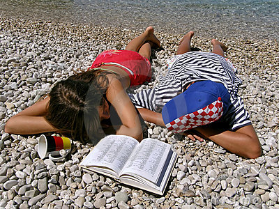 Germany girl and Croatian boy lying on stone beach