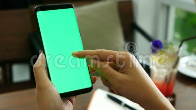 Gesamtlänge 4k nahe hohe Frauenhand, die intelligentes Telefon mit grünem Schirm an der Kaffeestube, unter Verwendung der Fingern stock footage