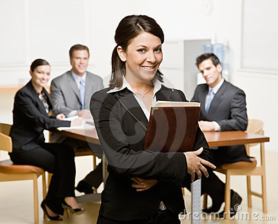 Geschäftsfrau mit Notizbuch und Mitarbeitern