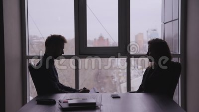 Geschäftsfrau am Schreibtisch, die gegenüber dem Mann Fragen stellt Junge Arbeitnehmerinnen interviewen männliche Person in einem stock footage