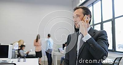 Geschäftsmann, der Entscheidungen während des Telefonanrufs im modernen Büro trifft, während Gruppe Geschäftsleute auf Sitzung te stock video