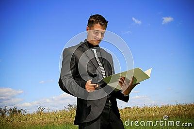Geschäftsmann mit Ordner und Mobiltelefon