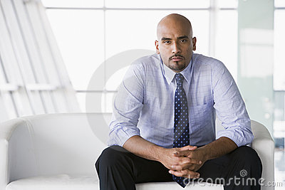 Geschäftsmann, der auf Sofa in der Vorhalle sitzt