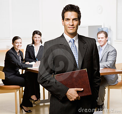 Geschäftsmann mit Notizbuch und Mitarbeitern