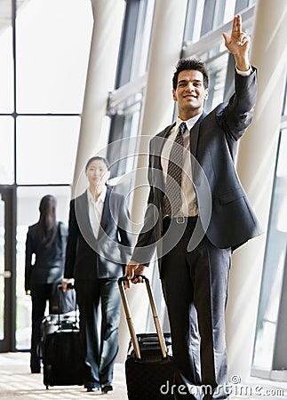 Geschäftsreisender, der Koffer und das Gestikulieren zieht