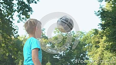 Geschickter junger Spieler, der den Ball auf dem Spielplatz spielt und dabei Hit, Zeitlupe praktiziert stock video footage