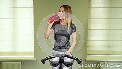 Geschikt jong vrouwen drinkwater in de gymnastiek Spiervrouw die onderbreking na oefening nemen stock footage