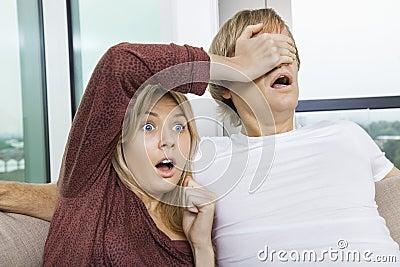 Geschokte vrouw die man ogen behandelen terwijl thuis het letten van op TV