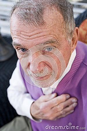Gesicht des ernsten älteren Mannes, der entlang der Kamera anstarrt
