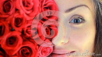 Gesichtsnahaufnahme einer schönen jungen Frau mit roten Rosen stock video footage