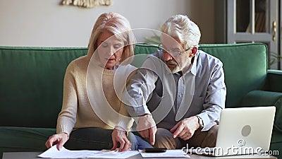 Gesorgte alte Paare betonten über die unbezahlten Bankverbindlichkeiten, die Rechnungen halten stock footage