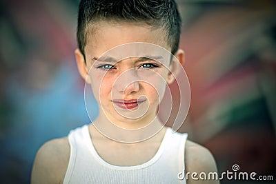 Gespannen jongen tegen graffitimuur
