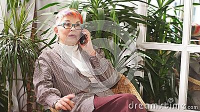 Gestionando activamente a una empresaria de alto nivel sentada en la silla en un centro de negocios lleno de plantas verdes metrajes