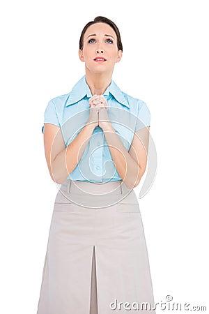 Gestörte junge betende Geschäftsfrau