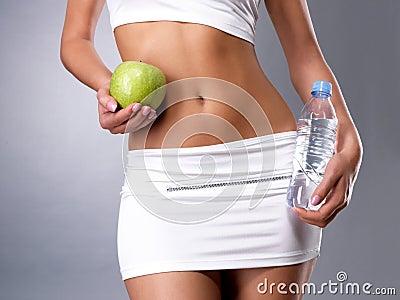 Gesunde weibliche Karosserie mit Apfel und Wasser