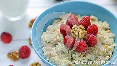 Gesundes Frühstück - Hafermehl mit den frischen, reifen Himbeeren und den Walnüssen in einer Schüssel, die auf einem Holztisch st stock video