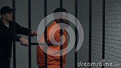 Gevangenisveiligheidsagent die Afrikaans-Amerikaanse gevangene duwen, die geweld, misbruik gebruiken stock video