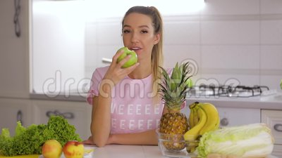 Gezond ontbijt, gelukkige glimlachende vrouw die groene verse appel op keuken eten stock videobeelden
