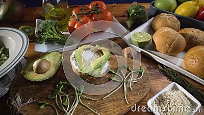 Gezond voedsel Gezond assortiment van groenten en vruchten met peulvruchten: sandwich met ontsproten avocado en sesam, stock footage