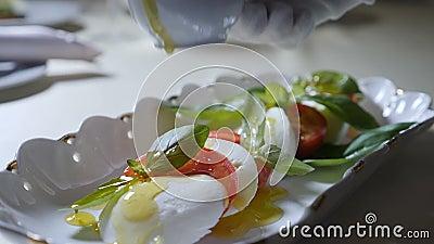 Gezond voedsel en vegetarisch concept Sluit omhoog van het gieten van olijfolie over caprese salade Italiaanse caprese salade met stock video