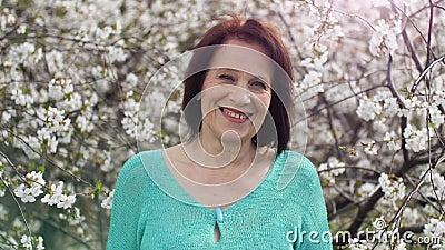 Gezonde lachende vrouw in de buurt van bloeiende boom stock footage