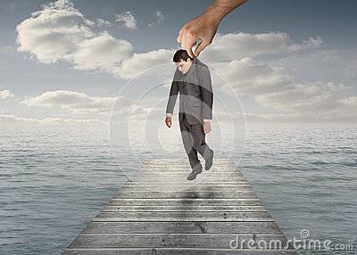 Giant hand holding a businessman by his jacket