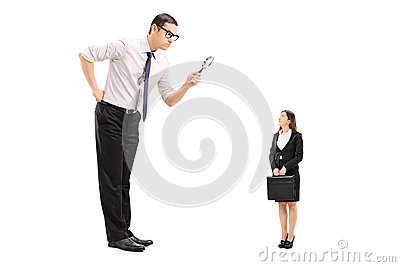 Giant man looking at woman through magnifier