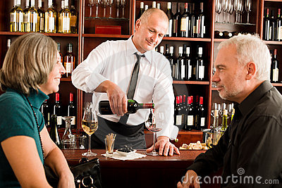 Gießen älterer Paarbarkellner des Weinstabes Glas