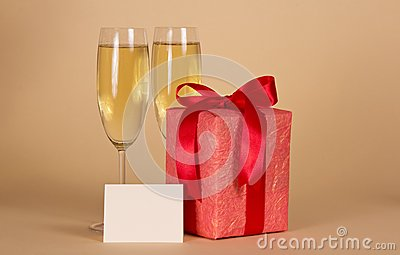 Gift box with a bow, empty card and wine glasses