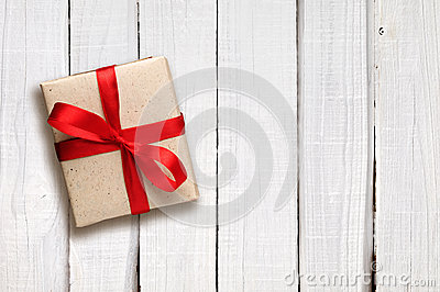 Gift box with red bow on white wood