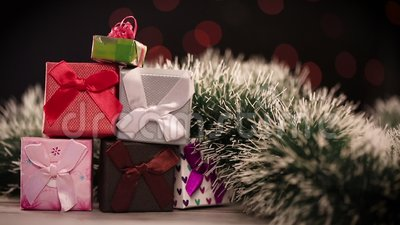 Gift boxes and christmas tree on table with lights in background stock video