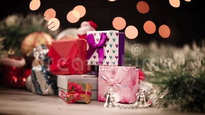 Gift boxes and decorations on table with lights in background stock video footage