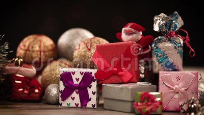 Gift boxes and decorations on table with lights in background stock video