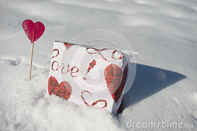 Gift and heart shaped lollipop in the snow