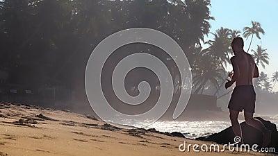 Gimnastyczka biega wzdłuż żółtej piaskowatej plaży z brąz skałami zdjęcie wideo