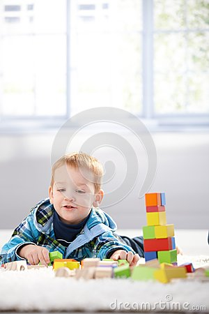 Ginger-haired toddler playing with cubes smiling