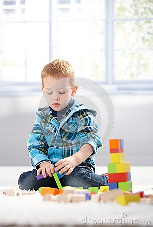 Ginger-haired toddler playing on floor